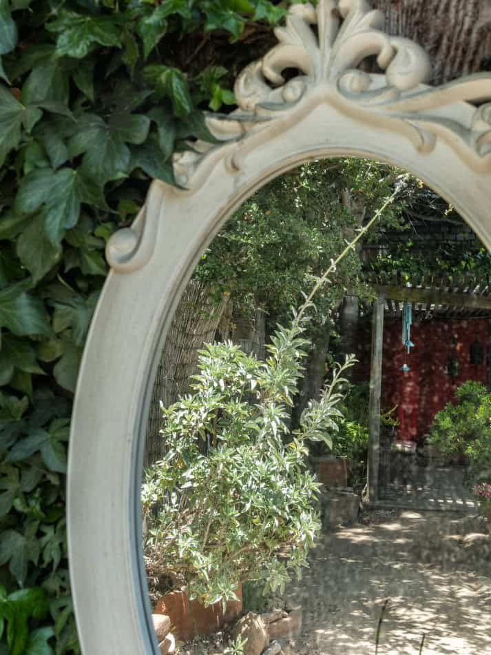 Photo of ornamental garden mirror with reflection of gravel pathway and some plants