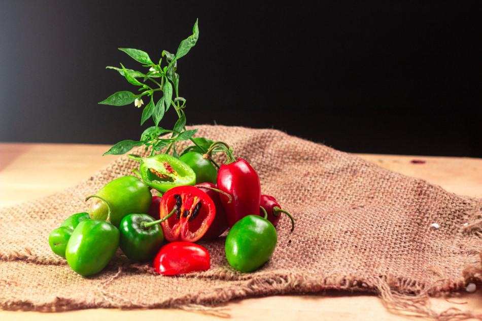 Photo of red and green Rocoto Manzano peppers on a burlap bag that are native to Peru