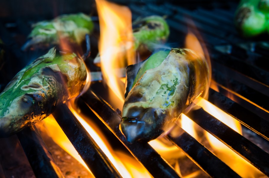 Photo of two green chili peppers being fire roasted on a grilll