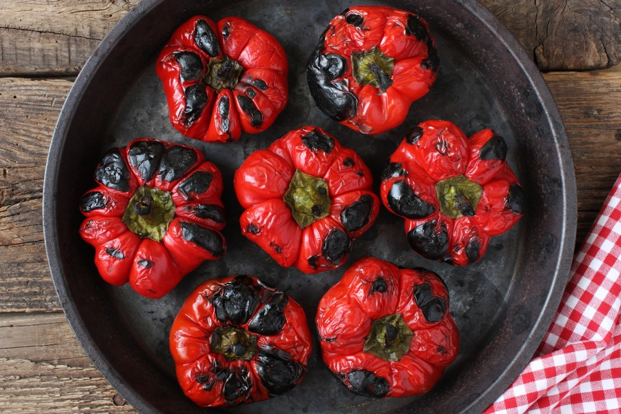 Photo of 7 roasted red bell peppers with charred toped