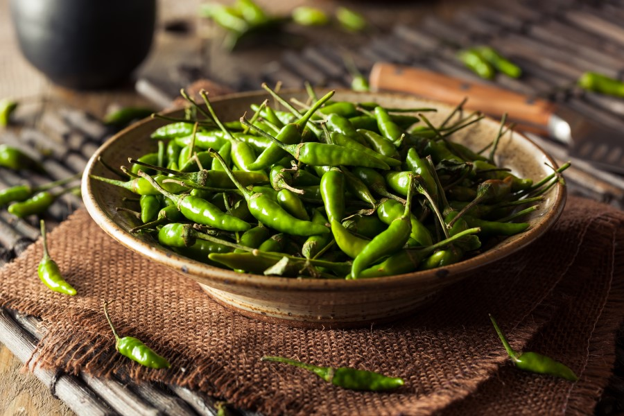 Many small green Thai chili peppers sitting in a brown bowl on top of a brown placemat
