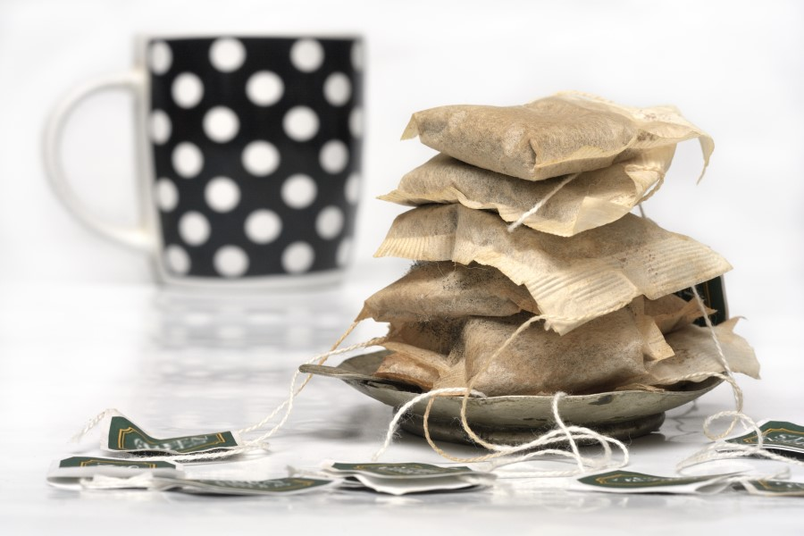 Photo of used teabags stacked on each other with a mug in the background