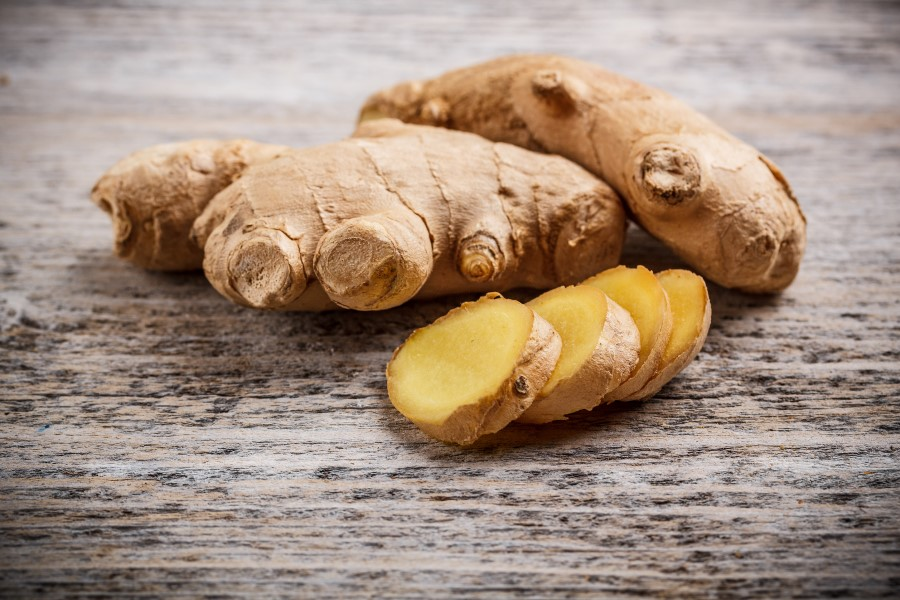 Photo of whole and sliced ginger set on a wooden table